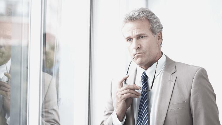 窓の外を眺めるスーツ姿のビジネスマン
