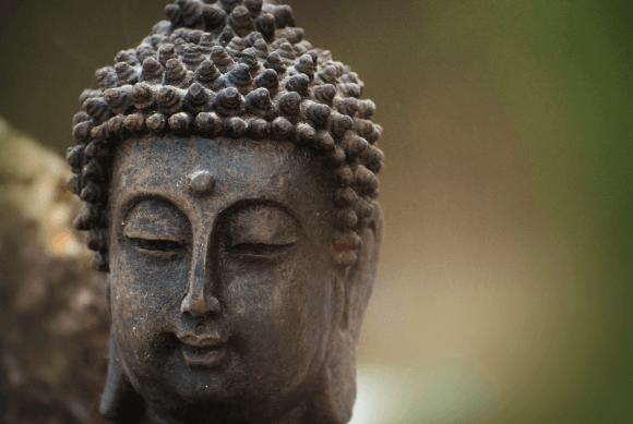 Kopf einer Buddha-Figur vor verschwommenem Hintergrund