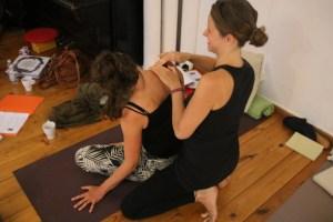 Zwei Teilnehmerinnen der Yogalehrer Ausbildung in Berlin üben hands on. Hands on, auch Assists genannt, gehören selbstverständlich zu den praktischen Teilen dieser Yoga Ausbildung dazu. Dr. med. Wiebke Mohme weiß als Ärztin genau, worauf es wirklich ankommt. Leider gibt es durch Yoga viele Verletzungen. Dem gilt es vorzubeugen. Im Yoga geht es darum sowohl die Gesundheit zu unterstützen, als auch präventiv zu arbeiten. In keinem Falle dürfen Verletzungen durch die Yogapraxis selbst entstehen!