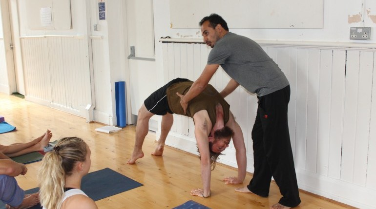 Teacher showing Yoga students Urdvha Danurasana