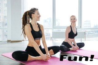 Two cheerful attractive young women stretching on pink yoga mats