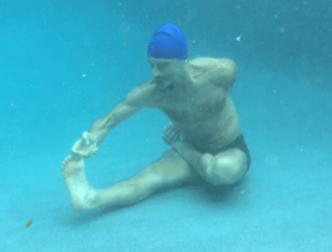 Underwater active half bound lotus forward bend on exhalation retention, by Simon Borg-Olivier
