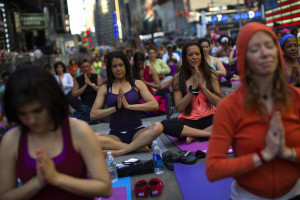 People take part in a group yoga practice on the morning of the summer solstice in New Yorks Times Square  Путешествие йоги в Америку: йога в Америке