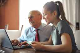 young woman helping senior man with payment on internet using laptop
