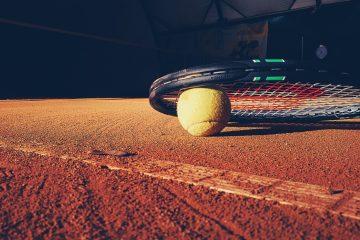 Tennisschläger liegt mit einem Tennisball auf dem Boden eines Tennisplatzes