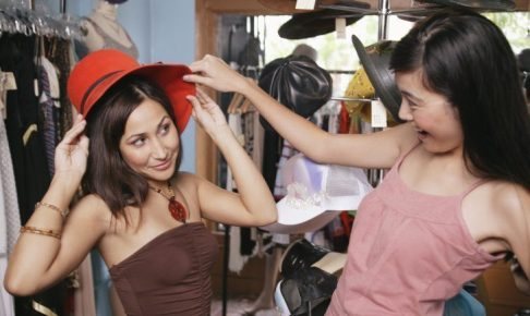 Two women trying on hats