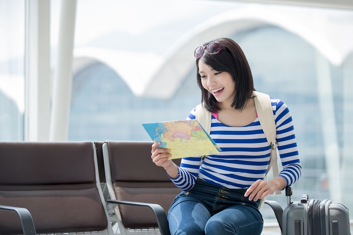 beauty woman take map and smile happily in hong kong airport, asian
