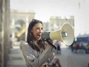 cheerful young woman screaming into megaphone