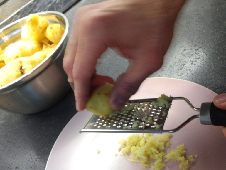 Ginger is being grated with a hand grater.