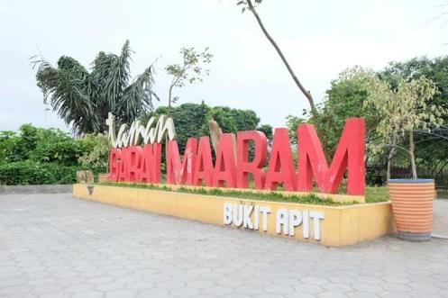 "Ada tulisan ""Bukit Apit"" di bagian bawah (merupakan nama kelurahan tempat terdapatnya taman ini)"