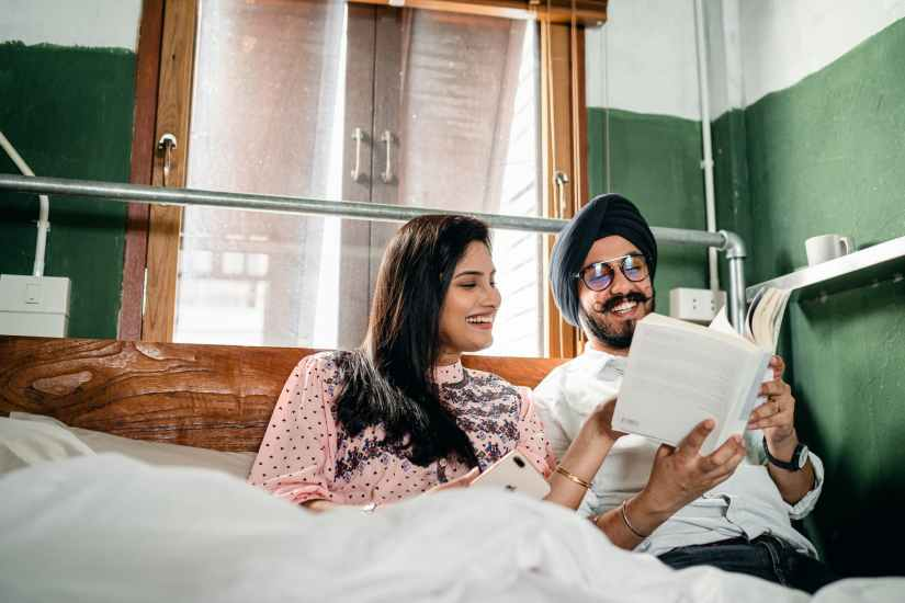 happy couple reading book and communicating cheerfully at home