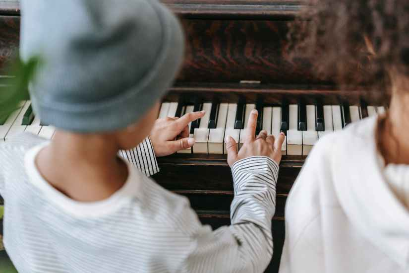 unrecognizable ethnic children playing piano at home