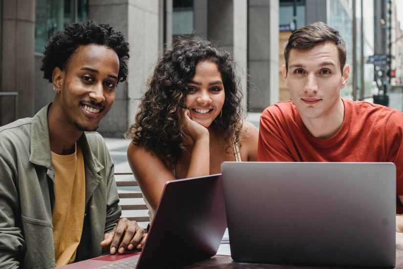 multiracial students working on laptop in street