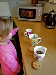 Helping to make a cup of tea to enjy with biscuits.