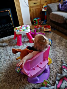 My daughter Beast sitting in the Fisher Price Laugh and Learn Smart Changes Chair.