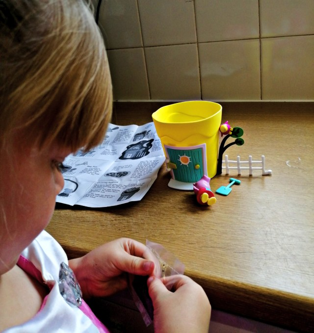 Pig opening the seed sachet for the peppa pig growing pot.