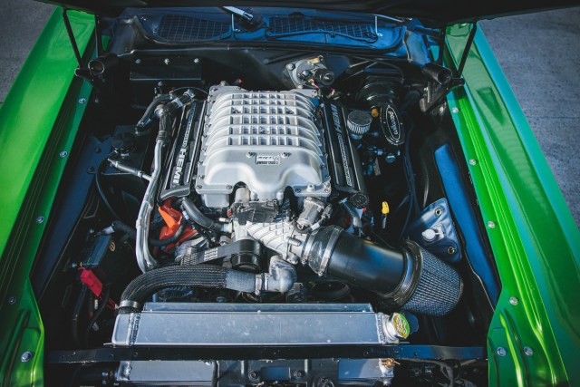 A view of the Modern Dodge Hellcat engine inside the engine bay of this 1974 Dodge Challenger.