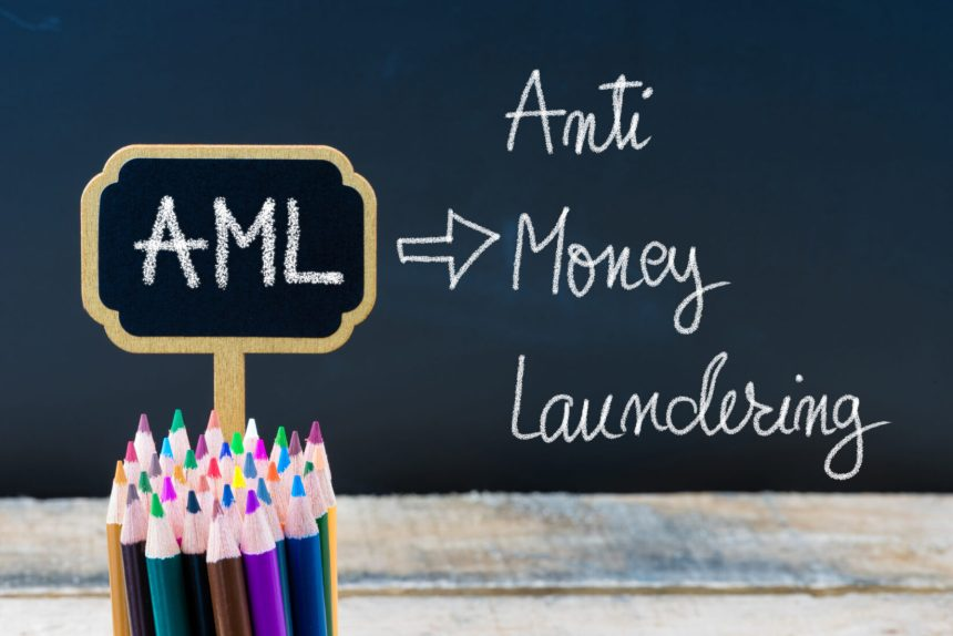 Business Acronym AML Anti Money Laundering written with chalk on wooden mini blackboard labels and chalkboard background.