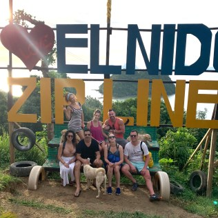 mix of happy people sitting underneath the i heart el nido zipline sign in philippines