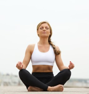 Portrait of a beautiful young woman sitting in yoga pose outside