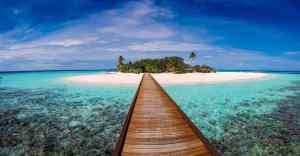 Long wooden board walk over water in the Maldives.