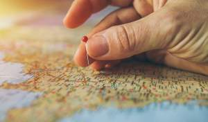 Hand sticking a pin in a map.