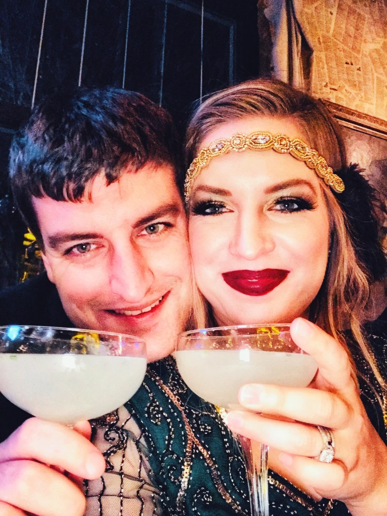 Man and women dressed in 1920's flapper attire with martinis.