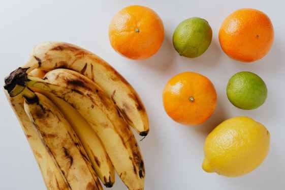 photo of citrus fruits beside banana