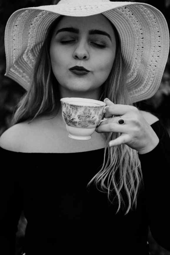 gorgeous woman in hat drinking coffee