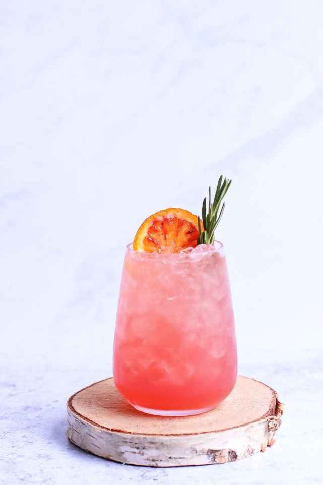 tasty beverage with orange slice and rosemary sprig