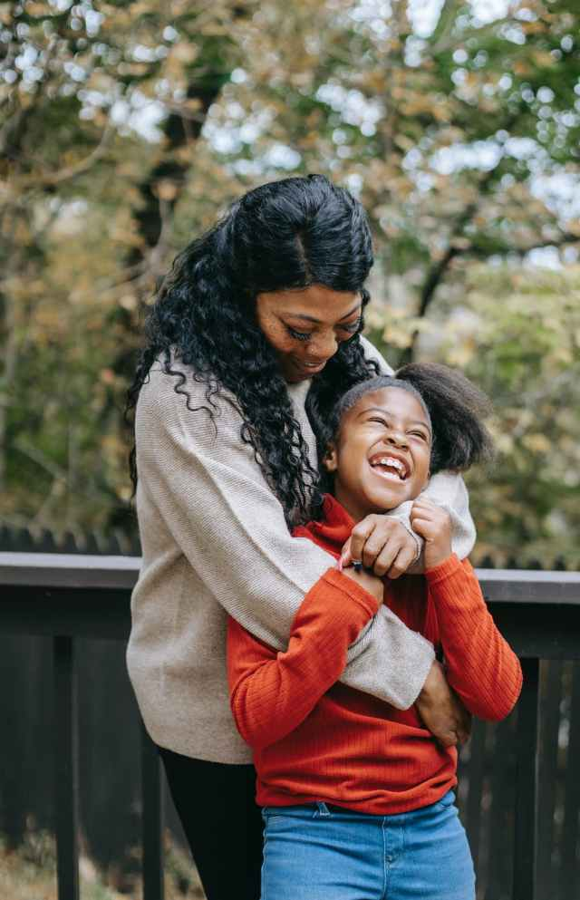 black mother embracing happy daughter near fence