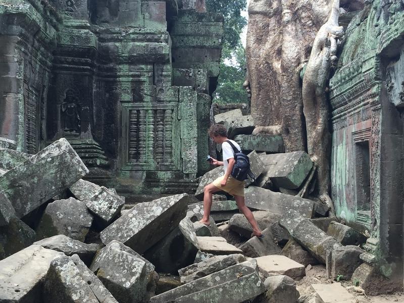 Man climbing ruins at Ta Prohm