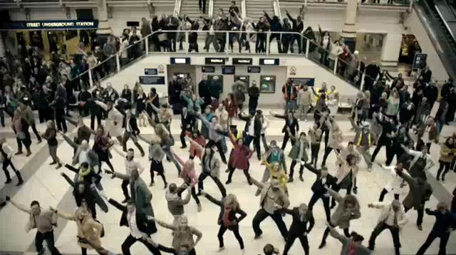 A bunch of people being in a flash mob at a train station.