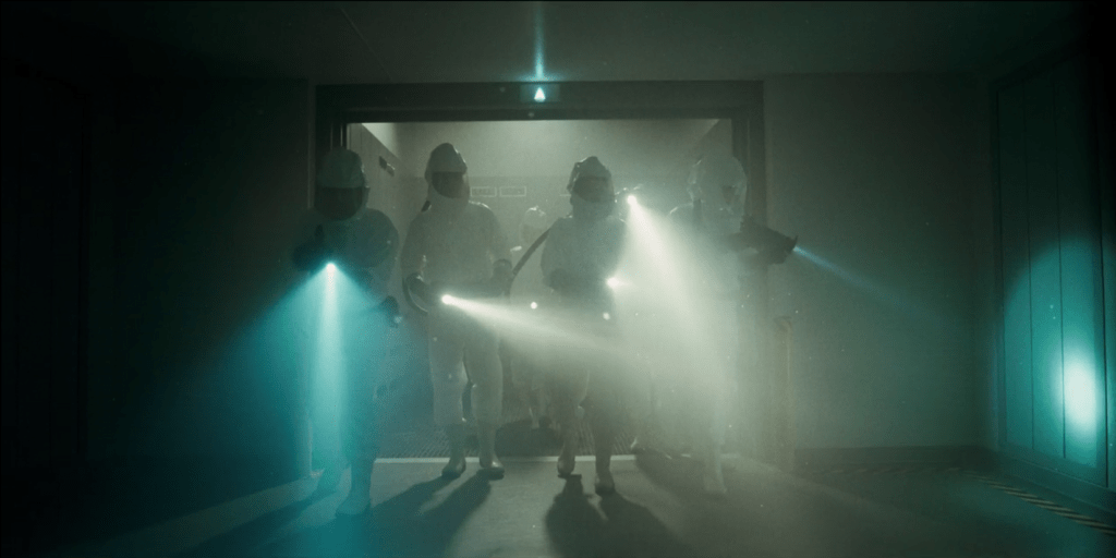 A bunch of scientists in hazmat suits standing in a spooky-ass corridor with their flashlights out