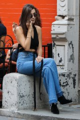 New York, NY - Bella Hadid looks sultry while grabbing lunch in the Big Apple! The supermodel shows off her long legs and toned figure in a pair of high waisted flares with frayed hem, ankle boots, wrap around crop top, accessorized with a large cross choker, and bracelets. She shows off her Moschino phone case as she takes a phone call outside the restaurant. AKM-GSI October 19, 2016 To License These Photos, Please Contact : Maria Buda (917) 242-1505 mbuda@akmgsi.com sales@akmgsi.com or Mark Satter (317) 691-9592 msatter@akmgsi.com sales@akmgsi.com www.akmgsi.com