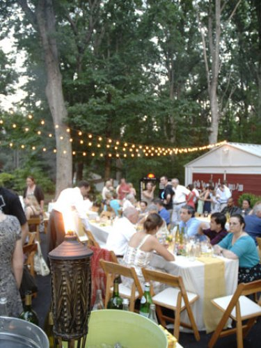 affordable backyard wedding reception in driveway with rented tables, cafe lights strung above, and tiki torch