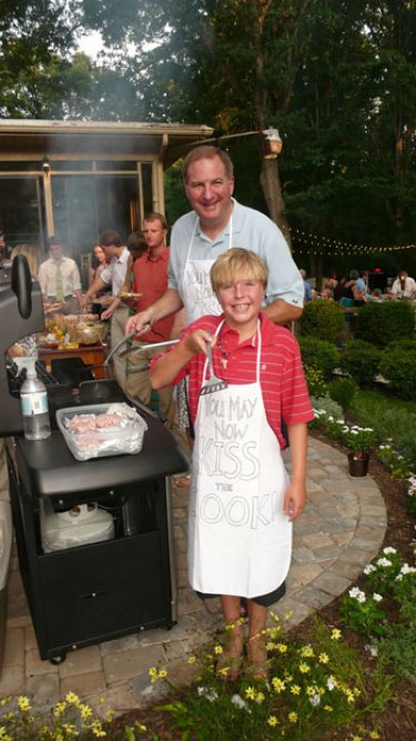 backyard garden wedding grill out with uncle and nephew of groom wearing You May Now Kiss The Cook apron