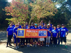 """Photo of young adults wearing bright cobalt blue tee shirts, many wearing sunglasses. the front 6 are holding a banner that reads, """"Volunteers in Action. Live United."""" United Way Logo."""