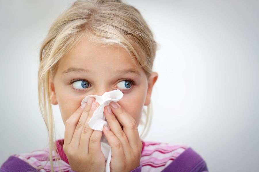Girl with flu blowing nose
