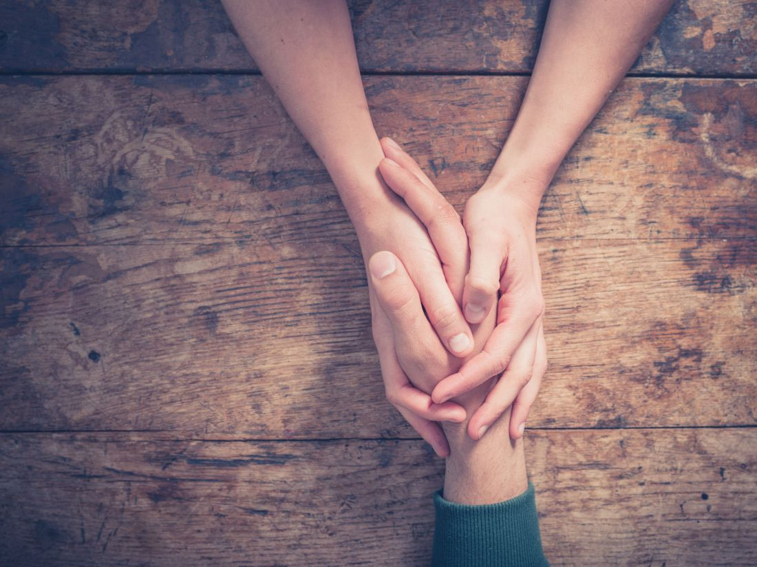 39280821 - close up on a man and a woman holding hands at a wooden table