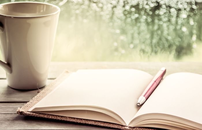 46750912 - pen on open notebook and coffee cup in rainy day window background, vintage filter