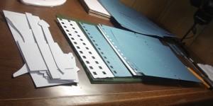 型紙をあてて裁断しているのは、青色の工作用紙です
