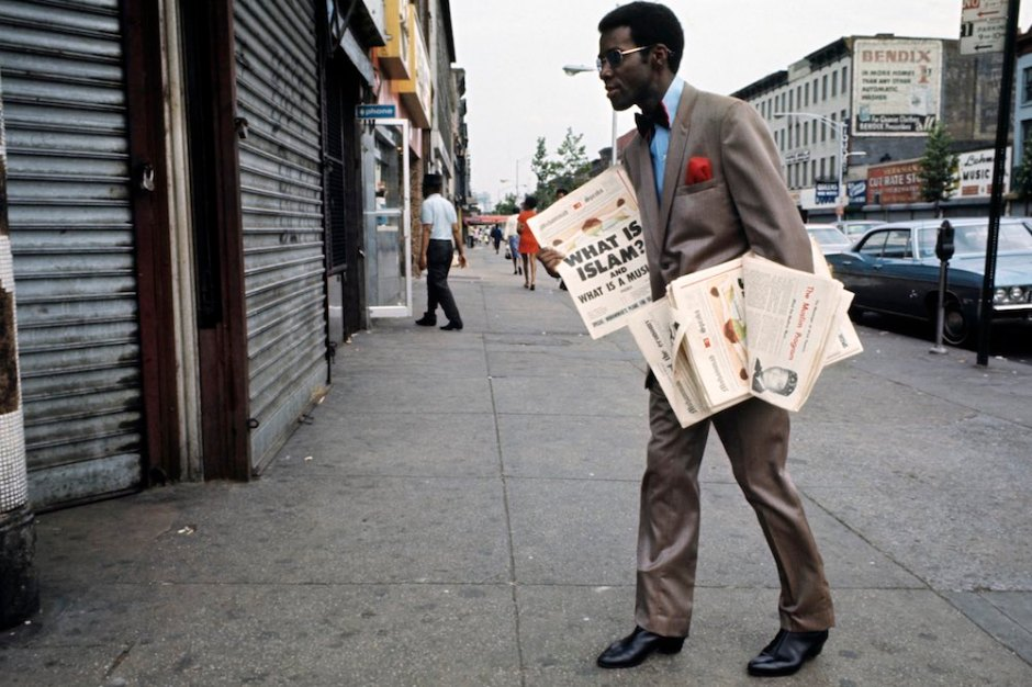 Harlem: The Ghetto. New York City- Harlem- juillet 1970: le ghetto; un afro-amÈricain trËs ÈlÈgant, costume et noeud papillon, vend ou distribue des journaux sur l'Islam et les musulmans dans une rue. (Photo by Jack Garofalo/Paris Match via Getty Images)