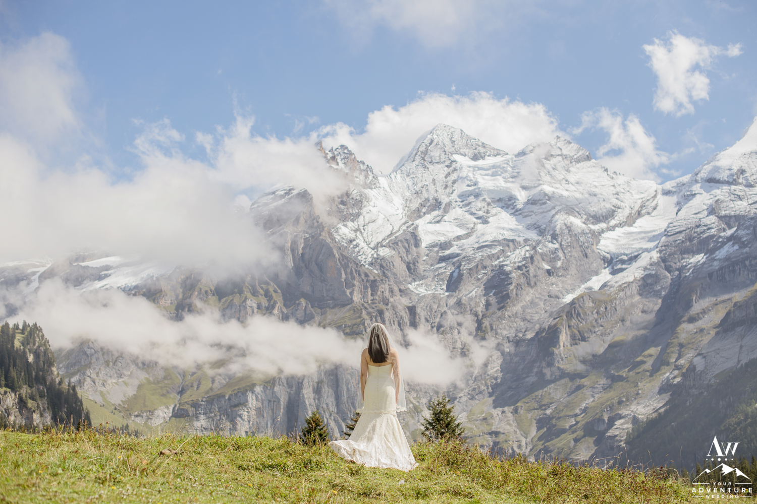 Bride standing in front of the Swiss Alps