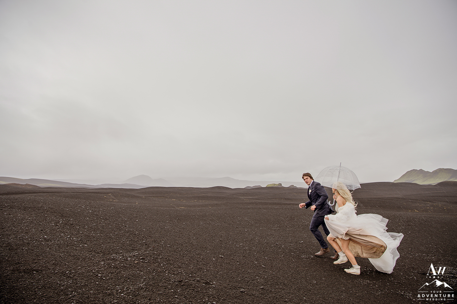 Couple Running through Rain during their Iceland Elopement