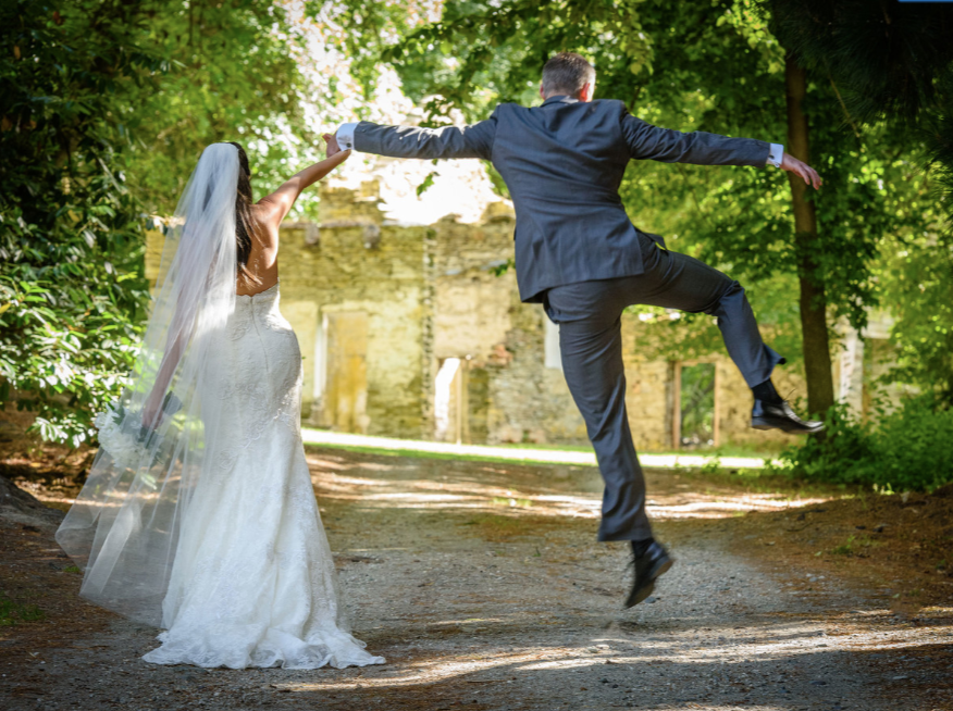 Groom and bride jumping in the air holding hands