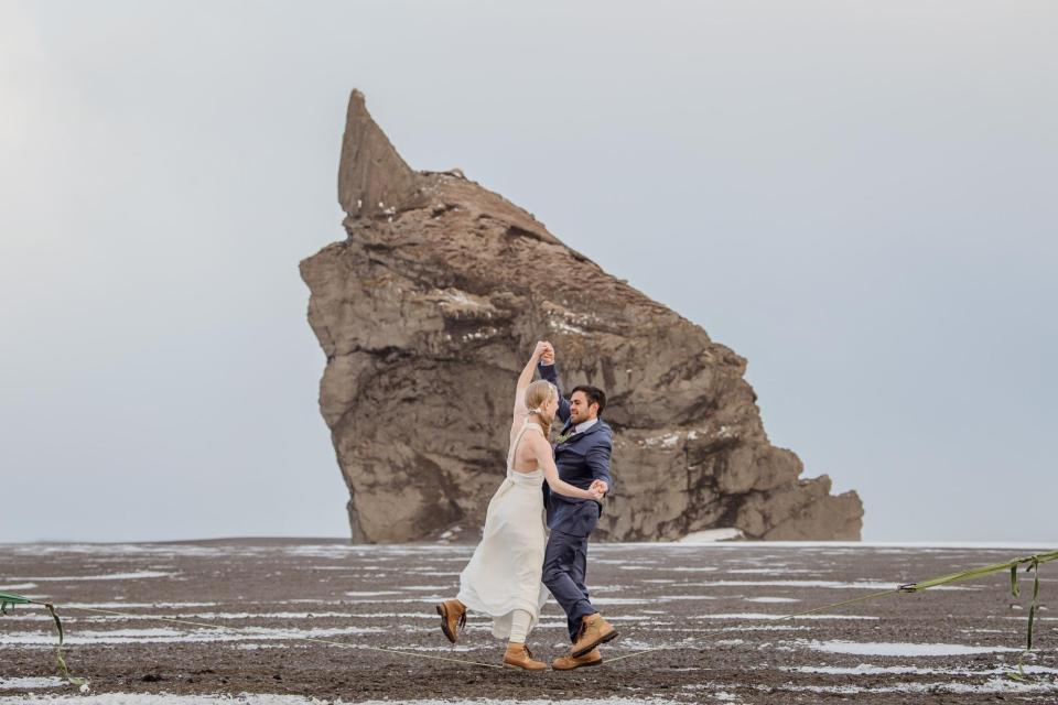 Bride and groom dancing on the wet sand beach