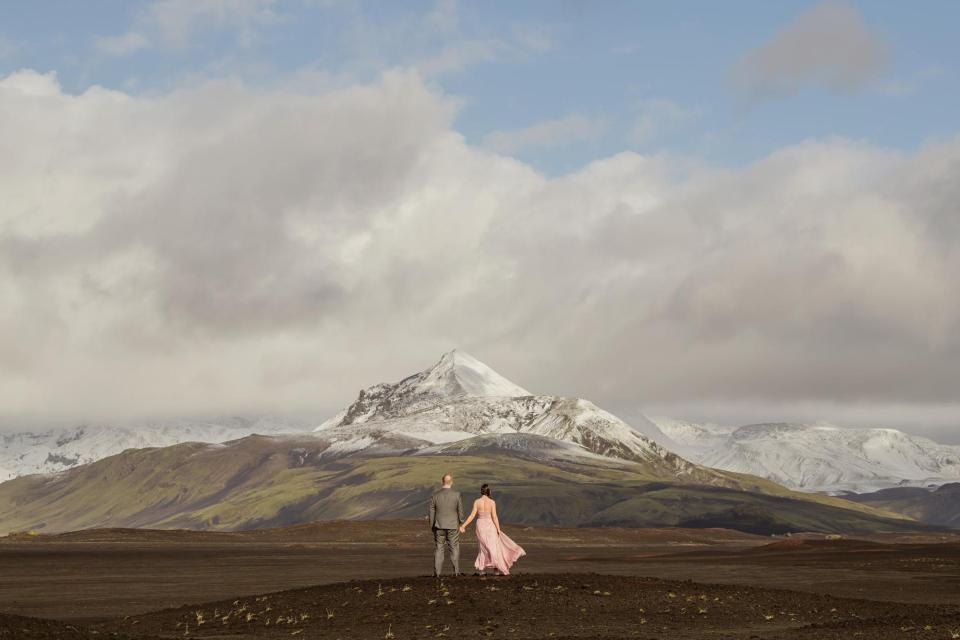 Bride in pale pink elopement dress with groom against mountainous landscape