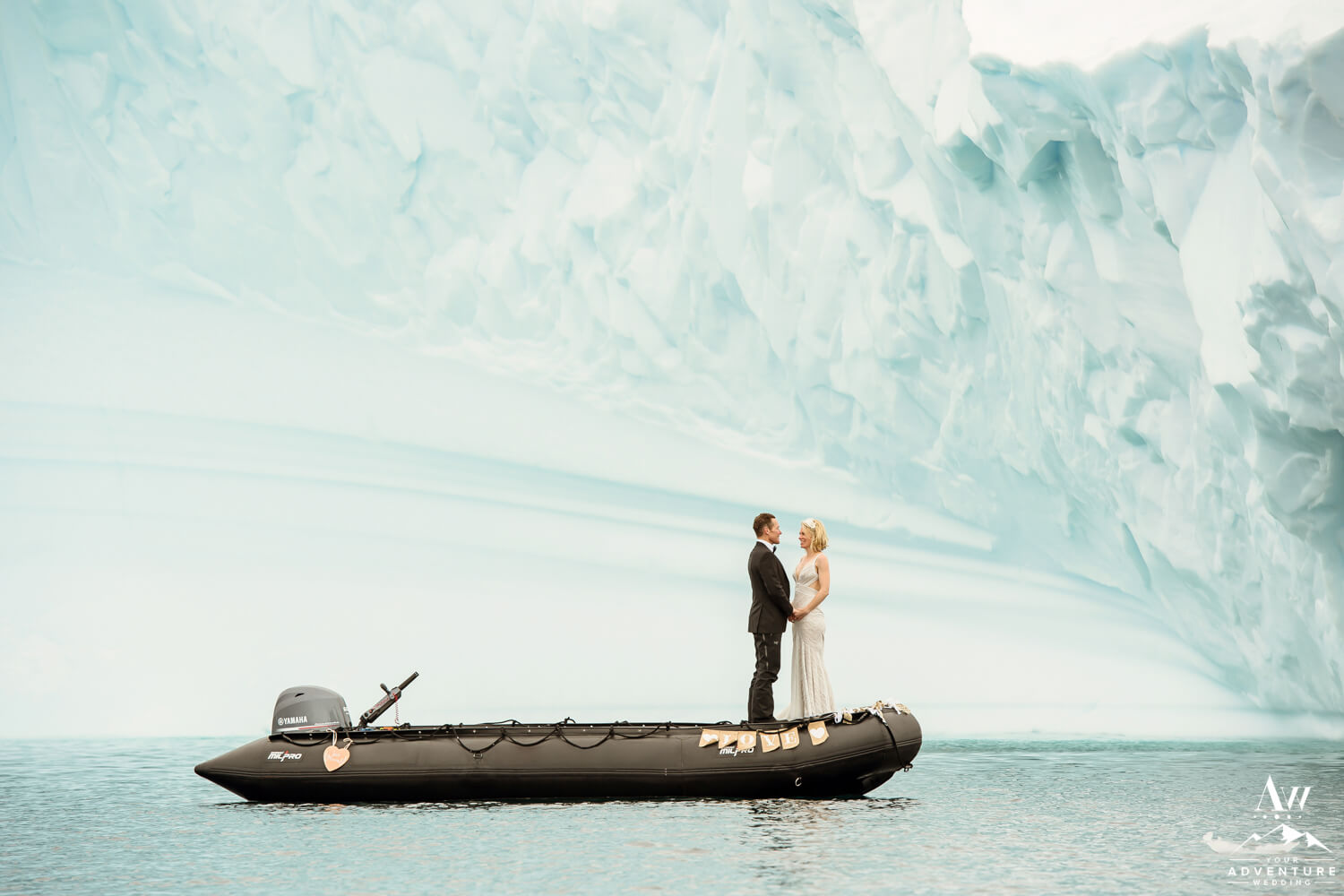 Antarctica elopement couple in a zodiac in front of an iceberg