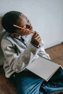 pensive black kid with notepad and pencil